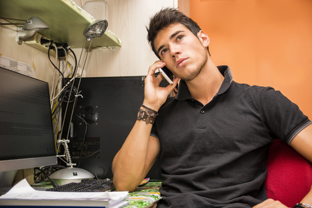 dorm: Waist Up Closeup of Young Attractive Man with Dark Hair Sitting at Computer Desk Talking on Cell Phone in Dorm Room Stock Photo