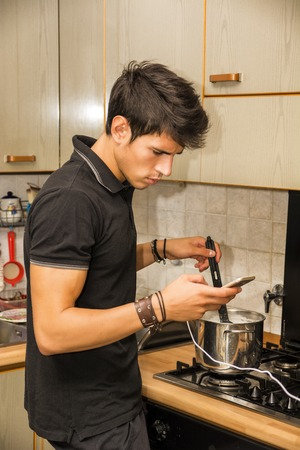 distracted: Distracted Young Man with Dark Hair Stirring Pot of Food on Kitchen Stove Top While Looking at Cell Phone Screen Stock Photo