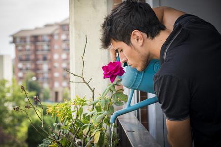 Hombre joven atractivo en Apartamento Balcón plantas de riego en el recuadro azul de regadera en Sunny Day con campo en segundo plano
