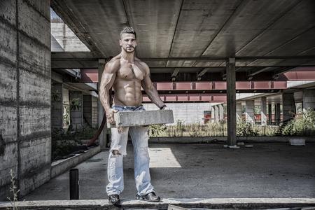 sexy construction worker: Sexy construction worker shirtless showing muscular body, holding big bricks Stock Photo