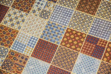floor covering: Tiled or linoleum floor covering with repeating square pattern, each square with smaller shapes, in mainly blue, gold and brown colors. Stock Photo