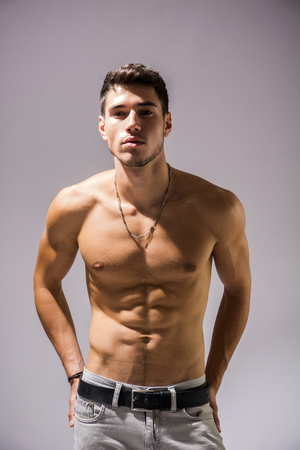 Handsome shirtless athletic young man in jeans, looking at camera in studio shot, isolated on white background