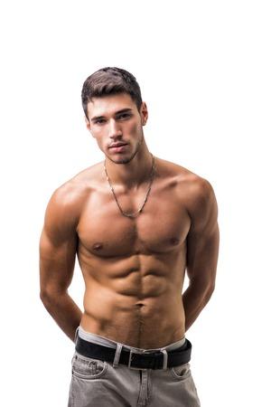白い背景に分離されたハンサムな上半身裸運動若い男のジーンズ、スタジオ撮影でカメラ目線