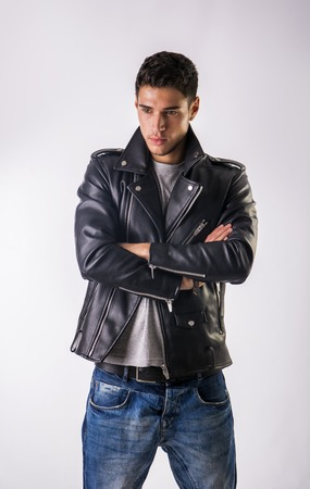 Handsome young man wearing leather jacket, t-shirt and jeans, on white background looking away Stock Photo