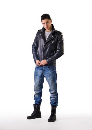 Handsome young man wearing leather jacket, t-shirt and jeans, on white background looking at camera
