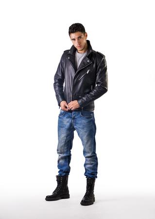 Stattlicher junger Mann, trägt Lederjacke, T-Shirt und Jeans, auf weißem Hintergrund Blick in die Kamera
