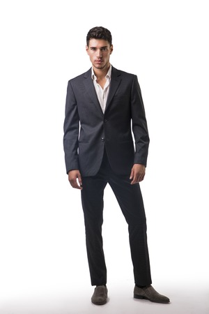 full figure: Young businessman confidently posing in front of camera, wearing suit isolated in white background. Full figure shot Stock Photo