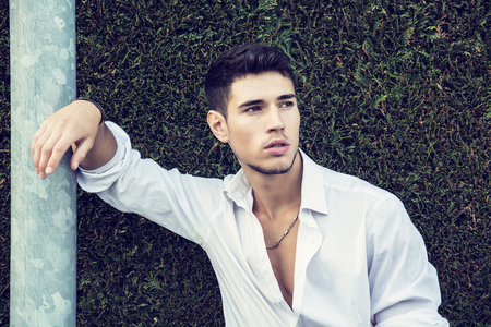 metal pole: Handsome young man in elegant white shirt standing outdoor in front of green bushy hedge looking away to a side, leaning against metal pole