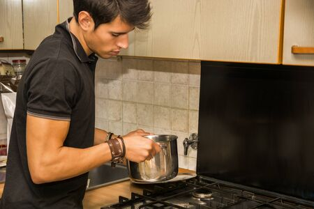 stove top: Distracted Young Man with Dark Hair Stirring Pot of Food on Kitchen Stove Top
