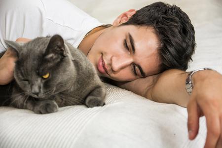 amigos abrazandose: Hermoso Joven Animal-Lover Man en una cama, abrazando y Caricias su gris Gato doméstico Mascota.
