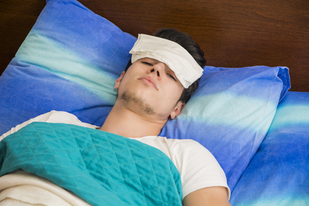 caucasian fever: Young handsome sick or unwell man in bed with a flu or fever Stock Photo
