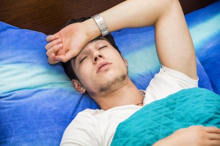 fiebre: Enfermo o indispuesto hermoso joven en la cama con una gripe o fiebre Foto de archivo