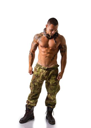 tatouage sexy: Cadrage Portrait d'homme musclé avec Crâne rasé permanent en studio avec fond blanc Wearing camouflé Imprimer Pantalons et Boa serpent enroulé autour du cou