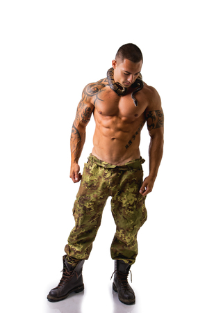 army boots: Full Length Portrait of Muscular Man with Shaved Head Standing in Studio with White Background Wearing Camouflaged Print Pants and Boa Snake Wrapped Around Neck