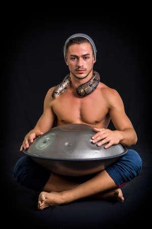 steel pan: Exótico Drumming Drummer Hombre con las manos en acero Pan Drums, mientras está sentado en el estudio aislado sobre fondo Negro