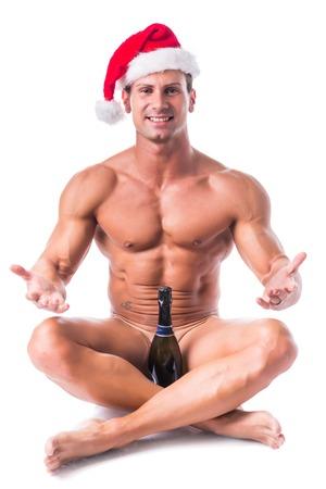 nackt: Naked muskul�ser Mann posiert im Studio mit Nikolausm�tze, isoliert auf wei�em Hintergrund Abdeckung Leistengegend mit Champagner-Flasche, Kamera l�chelnd betrachten