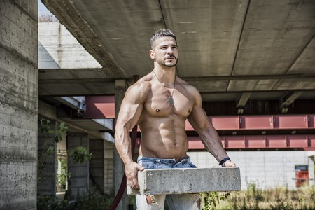 Sexy construction worker shirtless showing muscular body, holding big bricks Stock Photo