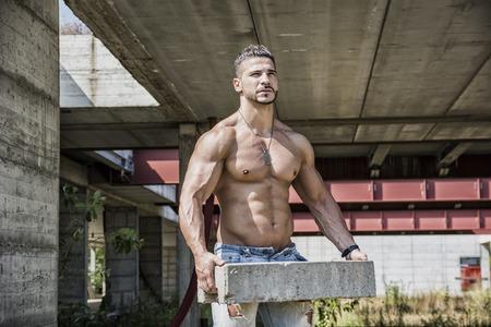 hombres sin camisa: Trabajador de construcción atractivo sin camisa mostrando cuerpo musculoso, la celebración de grandes ladrillos