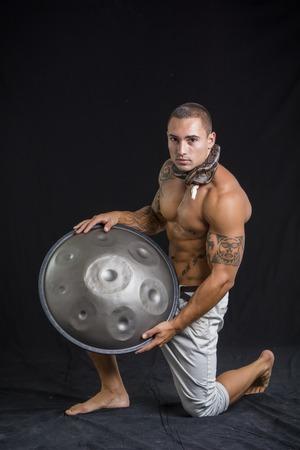 steel pan: Ex�tico Drumming Drummer Hombre con las manos en acero Pan Drums, mientras est� sentado en el estudio aislado sobre fondo Negro