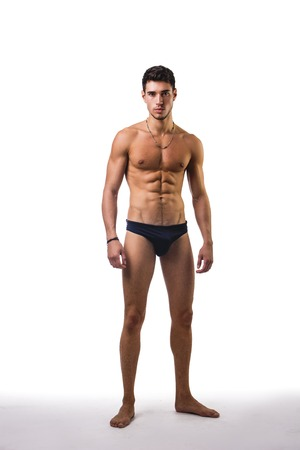topless: Handsome, fit young man wearing only underwear standing isolated on white background, looking at camera
