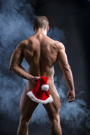 naked male body: Naked Muscular Man Posing in Studio with Dark Background Covering Bottocks Area with Santa Hat Stock Photo