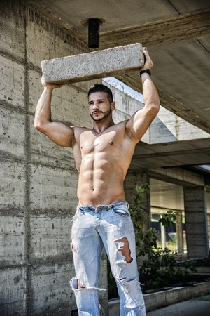 Sexy construction worker shirtless showing muscular body, holding big concrete brick