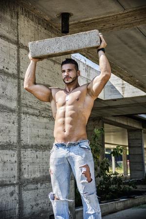 sin camisa: Trabajador de construcción atractivo sin camisa mostrando cuerpo musculoso, la celebración de grandes ladrillos de hormigón