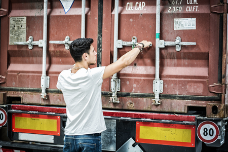 shipping supplies: Waist Up Portrait of Young Smiling Man Next to Freight Truck - Unloading Cargo from Container
