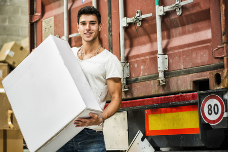 Waist Up Portrait of Young Smiling Man Holding Large White Box Next to Freight Train Car - Unloading Cargo from Train