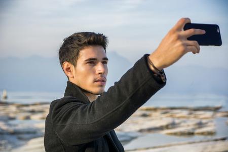 bel homme: Beau jeune homme sur un lac dans un endroit ensoleill�, journ�e paisible, prenant la photo de selfie avec le t�l�phone cellulaire Banque d'images