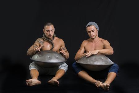 steel pan: Dos Drummers machos exóticos tamborileando con las manos en acero Pan Drums Mientras Sentados uno junto al otro en estudio, aislado sobre fondo Negro Foto de archivo