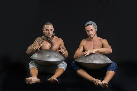 Two Exotic Male Drummers Drumming with Hands on Steel Pan Drums While Seated Beside Each Other in Studio, Isolated on Black Background