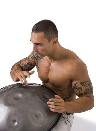 steel pan: Exótico que teclea del batería de sexo masculino con las manos en tambores de acero Pan, mientras está sentado en el estudio aislado en el fondo blanco