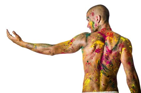 stretched out: Handsome young man seen from the back with skin all painted with Holi colors, isolated on white background, arm stretched out