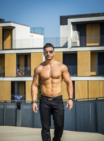 Attractive bodybuilder shirtless with baseball hat showing torso muscles, abs, pecs and arms, looking at camera