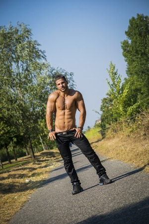 pecs: Attractive bodybuilder shirtless outdoor showing torso muscles, abs, pecs and arms, looking at camera in tilted photo