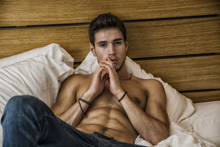 human chest: Shirtless sexy male model lying alone on his bed in his bedroom, looking at camera with a seductive attitude