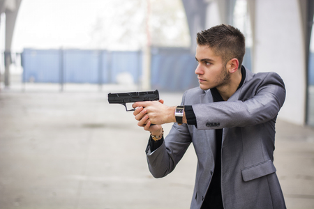 Well dressed handsome young detective or policeman or mobster standing in an urban environment aiming a firearm off to the left of the frame with a determined expression, side view Stock Photo
