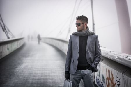 Красивый модный молодой человек, идущий по мосту в зимний период, неся металла портфель, носить солнцезащитные очки и шарф в туманный день
