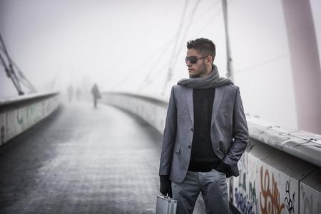 Knappe trendy jonge man lopen op een brug in de winter, het dragen van een metalen koffer, het dragen van een zonnebril en sjaal in een mistige dag