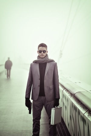 man relax: Young man in winter fashion standing outdoors in a warm overcoat and gloves, with a gun and a briefcase in hands, giving the camera a severe and stern stare behind his sunglasses Stock Photo