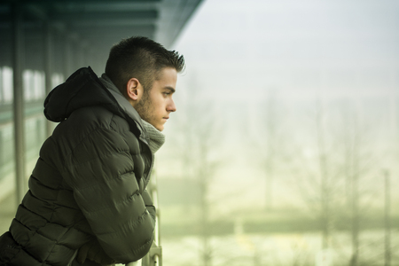 blue grey coat: Profile view of handsome young man outdoor in winter wearing scarf, looking away thinking