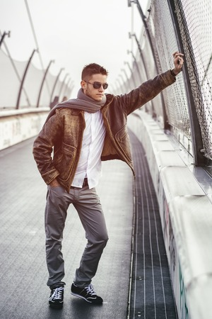 foreign bodies: Handsome trendy young man standing on a sidewalk wearing a fashionable jacket and scarf in a relaxed confident pose looking away down the bridge
