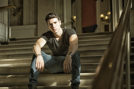 stitting: Young Handsome Man Stitting on Stairs Inside an Architectural Elegant Old Building While Looking at Camera