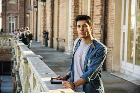 half body: Half Body Shot of a Thoughtful Handsome Young Man, a Tourist, Holding a Guide, Looking Away Outside Historic Building in European City