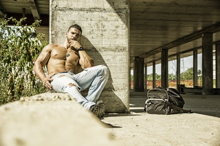 Muscle man shirtless outdoors in building site. Construction worker Stock Photo