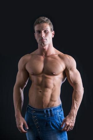 desnudo: Hombre atractivo joven con el torso desnudo muscular, vistiendo pantalones vaqueros, aislados en fondo negro