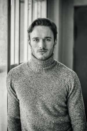 man portrait: Handsome serious man standing inside modern building next to big window, wearing wool sweater,  looking at camera Stock Photo