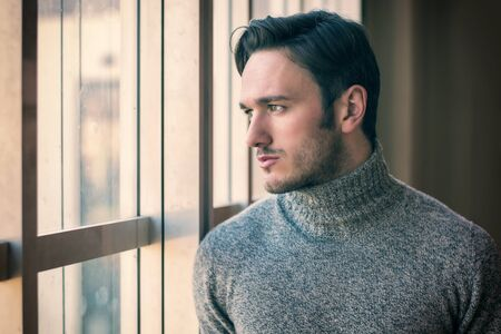 looking out: Handsome serious man standing inside modern building next to big window, wearing wool sweater,  looking out