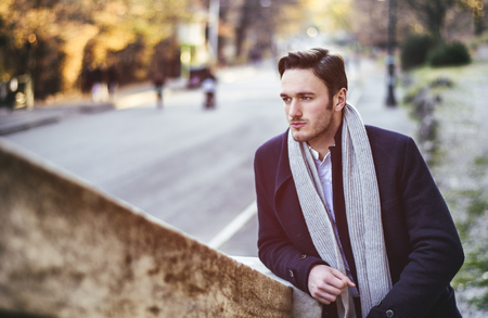 scarf: Handsome young man outdoor in winter fashion, wearing black coat and woolen scarf in city park Stock Photo